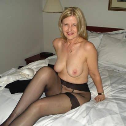 Frauenbrüste auf dem Bett